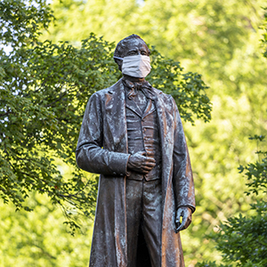 Photo of the Cornelius Vanderbilt statue wearing a face mask.